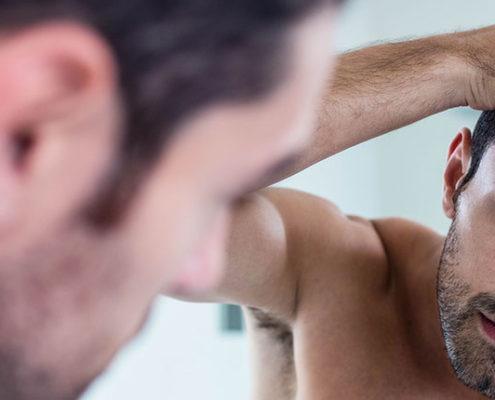 mand der sætter hår i spejlet